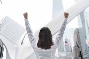 A woman rejoicing by raising her fists to the sky because she improved her financial wellness.