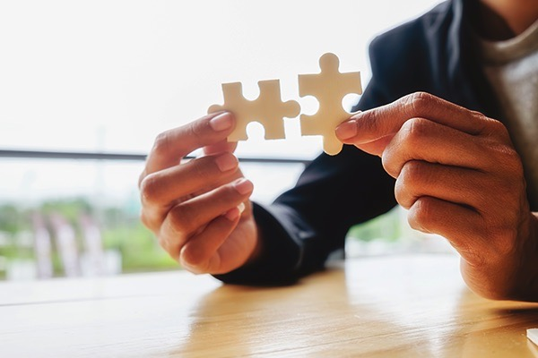 A pair of hands connecting two pieces of a puzzle while seated at a desk.