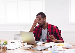A stressed man seated at his desk with his laptop surrounded by scraps of paper trying to manage his debt.