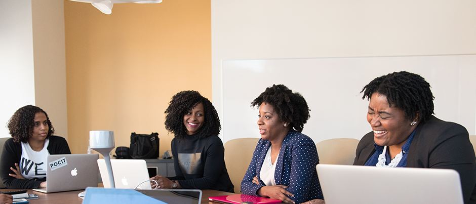 A group of women seated at a desk with their laptops discussing financial wellness for women.