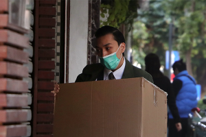 Mature male wearing a face mask while carrying a box of his belongings after being retrenched.