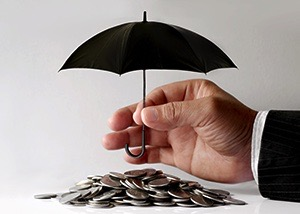 A hand holding a miniature version of a black umbrella above a pile of coins.