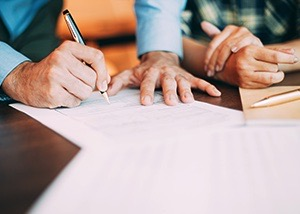 Older man examining and signing his last will and testament on a brown desk.