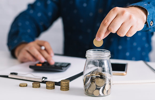 Male hands putting coins into a glass jar and calculating how much money his saving.