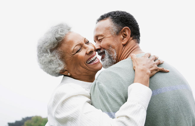 Elderly couple embracing their retirement by laughing and sharing a hug together.