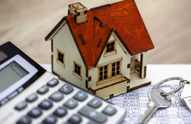 Miniature house with a set of keys next to a calculator as a symbol of owning your own home.